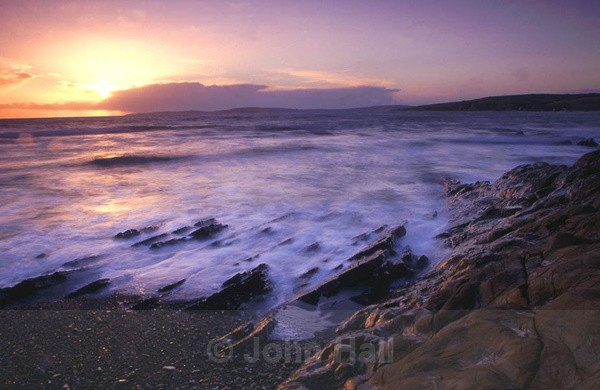 waves crashing on shoreline at sunset, garrettstown, co. cork, ireland.