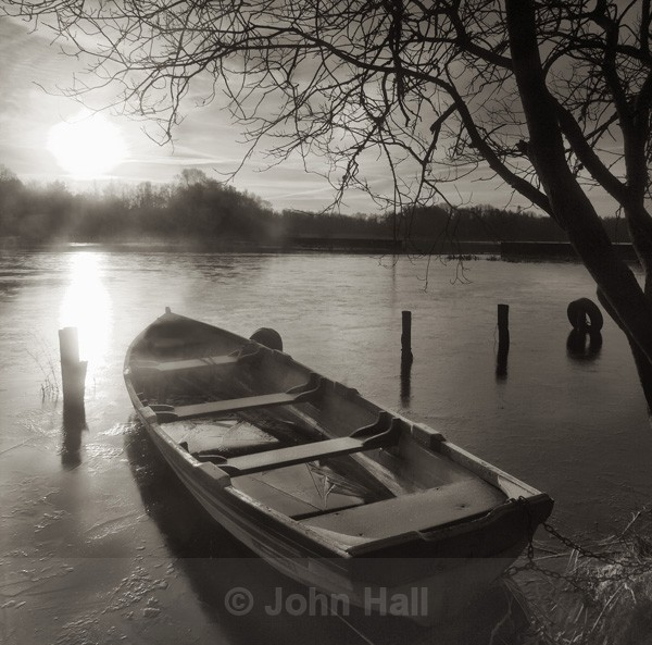 Monochrome study of a winter sunrise and boat on lough ennell, co. westmeath, ireland.