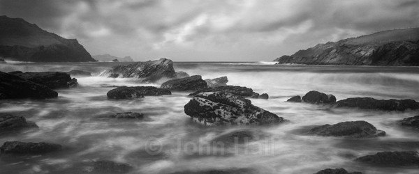 Fine Art Monochrome Of Waves Pounding The Rocky Shoreline At Clogher Beach, Co. Kerry, Ireland.