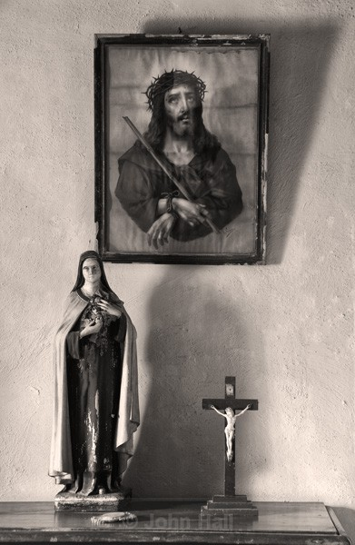 Fine Art Monochrome Of Religious Statue And Sacred Heart Picture On A Cottage Wall.