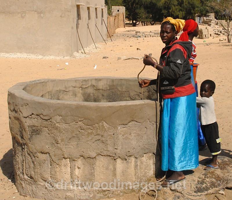Senegal Fulani village woman at well - Senegal Fulani Village