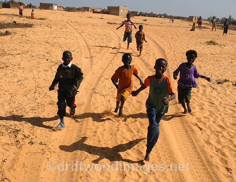 Senegal Fulani Village Fulani children running behind 4x4 - Senegal Fulani Village