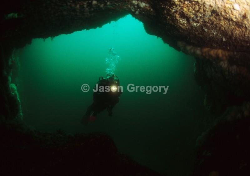 Diver explores natural arch - Diver exploring marine environment
