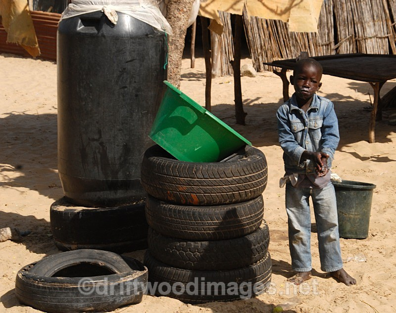 Senegal Fulani Village Fulani boy standing by tyres - Senegal Fulani Village