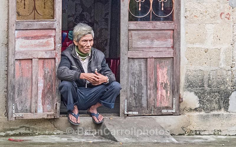 IMG_5169 Crouching man in doorway, Hue, Vietnam - Vietnam