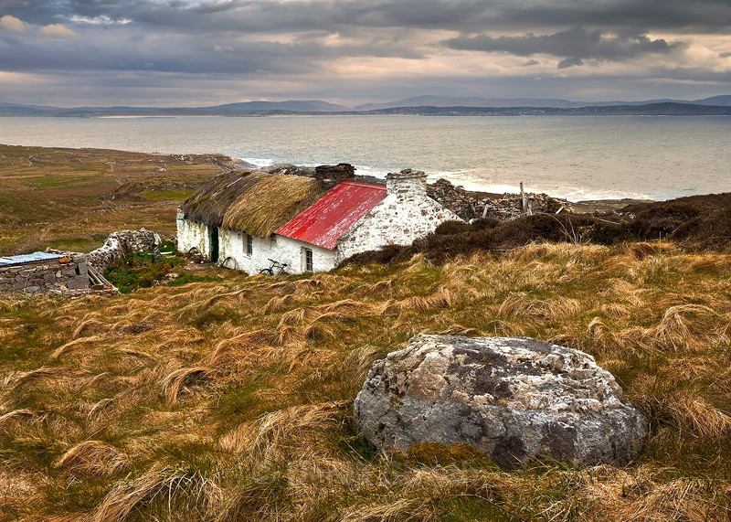 Old Irish Thatched Cottage on the hill overlooking the bay