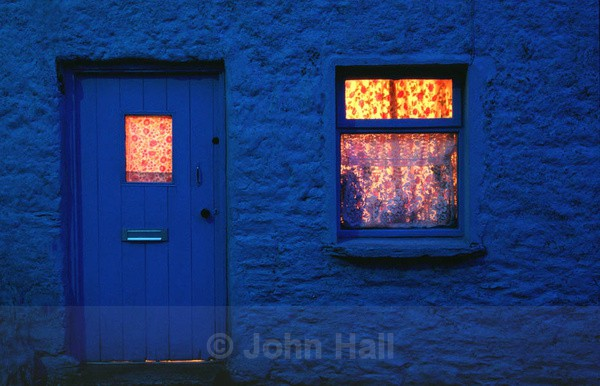 night image of blue cottage with light in window,co. kerry,ireland.